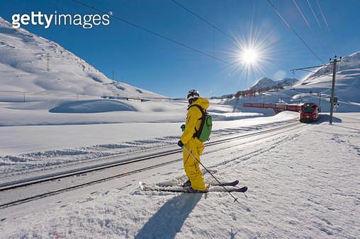 Skier beside railroad tracks, Diavolezza, Engadin, Canton of Graubuenden, Switzerland - gettyimageskorea