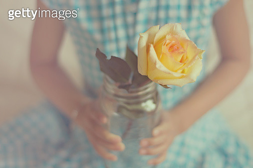 Girl in checked dress holding yellow rose in jar - gettyimageskorea