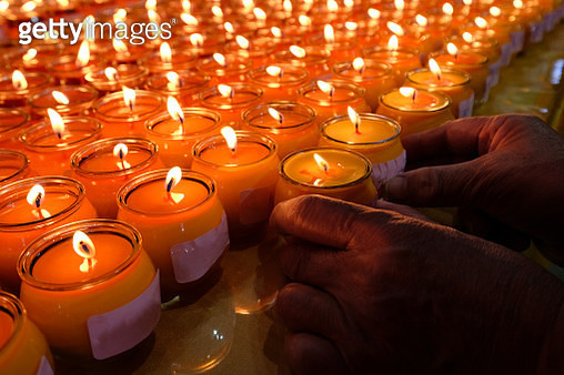 Butter lamps burning at a shrine with and old man hands holding the lamps - gettyimageskorea