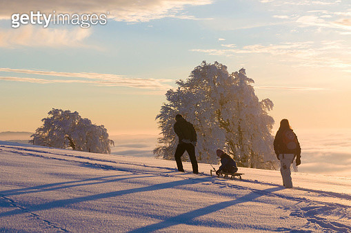 Winter landscape, family with a sled on Mt Schauinsland, Freiburg im Breisgau, Black Forest, Baden-Wuerttemberg, Germany, Europe - gettyimageskorea