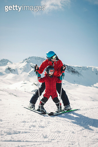 Full length of man teaching son to ski on snowy mountain - gettyimageskorea