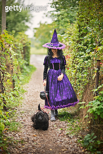 Little halloween witch walking with her dog - gettyimageskorea