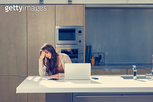 Woman doing paperwork with a laptop and digital tablet. - gettyimageskorea