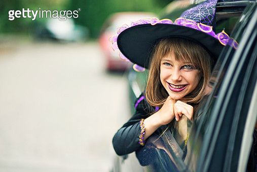 Little halloween witch smiling out of the car - gettyimageskorea