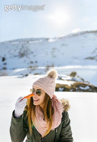 Spain, Asturias, happy young woman with carrot in snowy mountains - gettyimageskorea