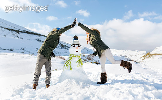 Spain, Asturias, couple with a snowman - gettyimageskorea