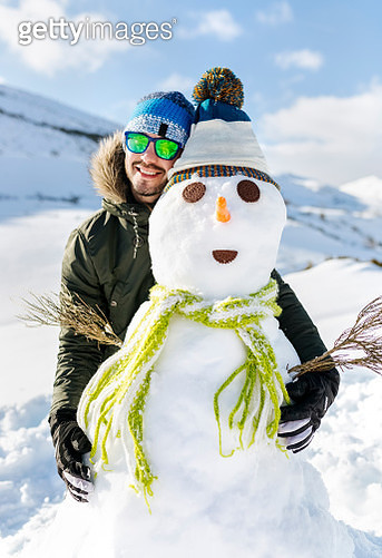 Spain, Asturias, happy young man with a snowman - gettyimageskorea