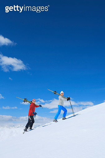 Snow skiers couple  Happy mature women and men carrying skis - gettyimageskorea