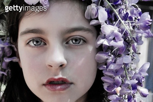 Close-up of young girl with wisteria in hair - gettyimageskorea