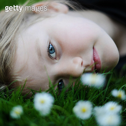 Girl lying on the grass with daisies - gettyimageskorea