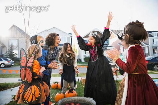 Exuberant girl in Halloween costume bobbing for apples - gettyimageskorea