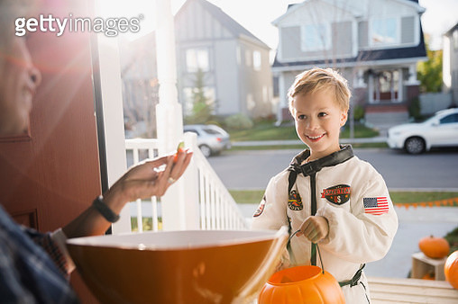Woman with candy greeting boy Halloween astronaut costume - gettyimageskorea