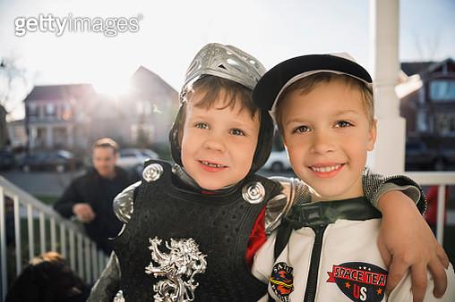 Smiling boys in Halloween costumes hugging front stoop - gettyimageskorea