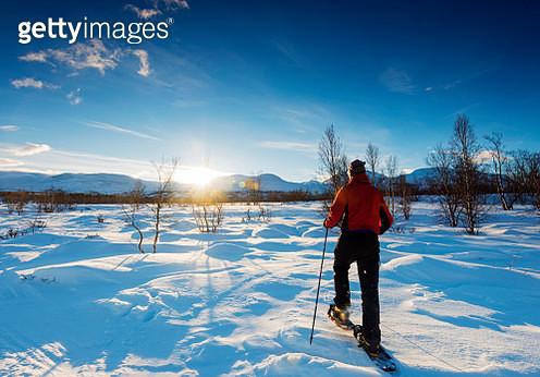 Sweden, Abisko, Abisko National Park, The Kings Trail (Kungsleden), Rear view of man in red jacket walking in snowed landscaped on skies, sun in blue sky, blue shadows on snow - gettyimageskorea