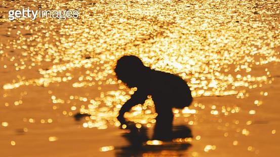 다대포해수욕장의 일몰 빛망울과 모래 놀이하는 아이의 실루엣 - gettyimageskorea