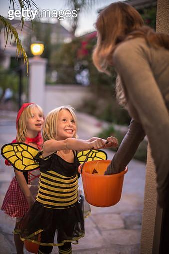 Woman putting sweets in girls' (4-5, 6-7) halloween buckets - gettyimageskorea