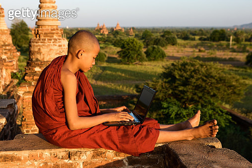 Young Buddhist monk using laptop - gettyimageskorea