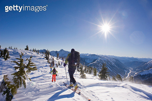 backcountry skiers climbing snowy mountain - gettyimageskorea