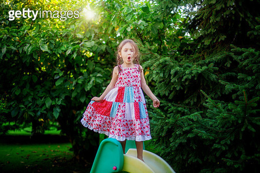 little girl playing on slide and singing - gettyimageskorea