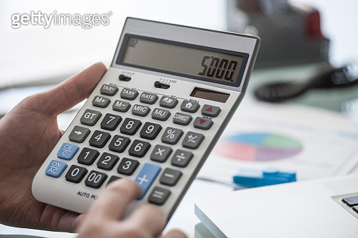 Close-up of man using a calculator in office - gettyimageskorea