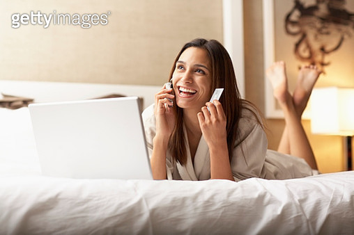 Woman Using Laptop and Cell Phone on Bed - gettyimageskorea