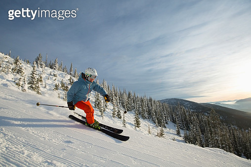Mature man on ski slope at sunset - gettyimageskorea