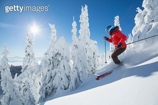 Mature woman on ski slope at sunlight - gettyimageskorea