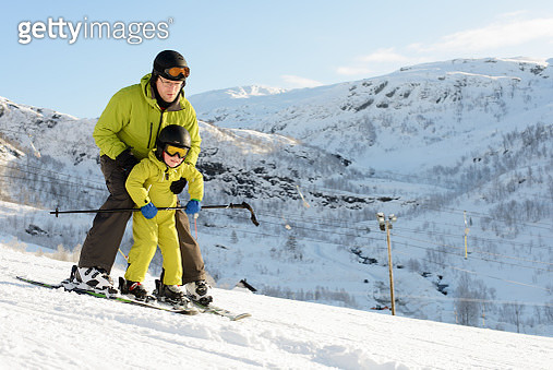 Father helps his son to ski down a ski slope - gettyimageskorea