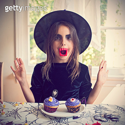 Girl with vampire teeth dressed as a witch for Halloween - gettyimageskorea