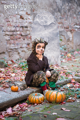 Boy in halloween costume sitting in cemetery - gettyimageskorea