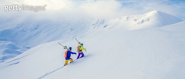 Two skiers climbing up a snow-covered hill - gettyimageskorea