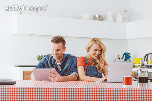 Adult couple using digital tablet and laptop at home - gettyimageskorea