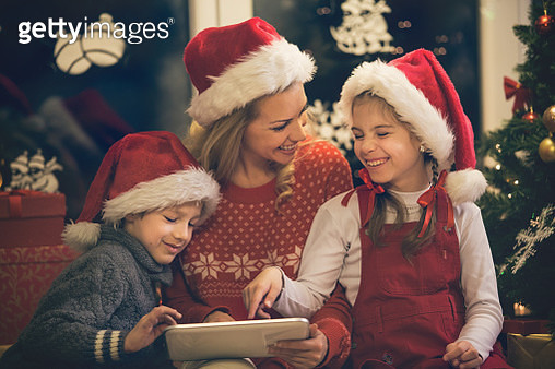 Mother and children having fun on digital tablet for Christmas - gettyimageskorea