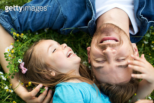 Father and daughter outdoors in a meadow. - gettyimageskorea