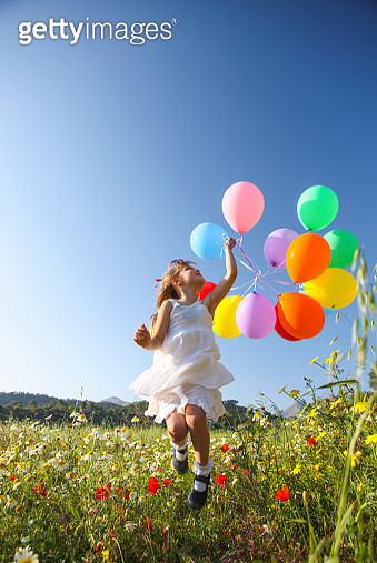 Girl jumping for joy with colorful balloons in wildflower meadow, Majorca, Spain - gettyimageskorea