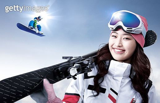 a woman holding a snowboard - gettyimageskorea
