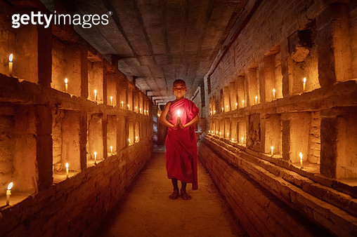 Novice Monk praying inside temple full burning candles Bagan Myanmar - gettyimageskorea