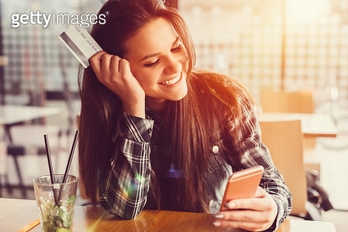 Girl holding credit card and texting - gettyimageskorea