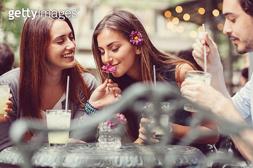 Young people drinking cocktails at sidewalk cafe - gettyimageskorea