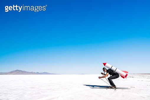 Skier with a rocket on his back on the desert. - gettyimageskorea