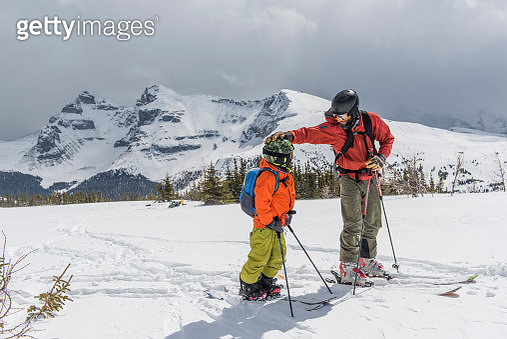 Father and son ski together in fresh snow,treeline - gettyimageskorea