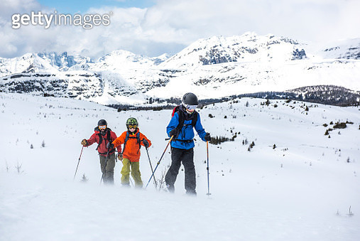 Father and sons ascend snow slope in wind,treeline - gettyimageskorea