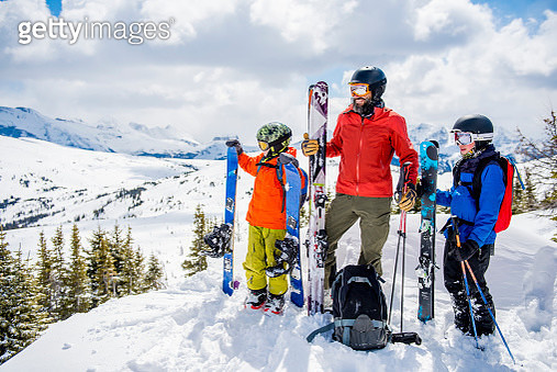 Father and sons relax in fresh snow, with skiis - gettyimageskorea