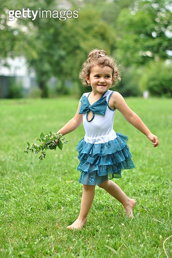 Little curly girl dancing on grass - gettyimageskorea
