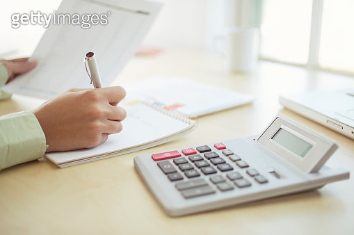 Woman at desk with a calculator and paperwork - gettyimageskorea