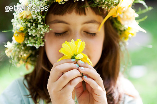 Portrait of little girl with wreath of flowers smelling yellow blossom - gettyimageskorea