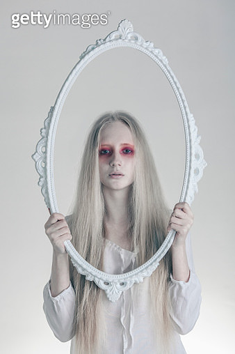 Portrait of woman with spooky red eyes holding picture frame against white background - gettyimageskorea
