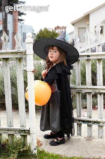 Girl (2-3) wearing witch costume holding pumpkin - gettyimageskorea