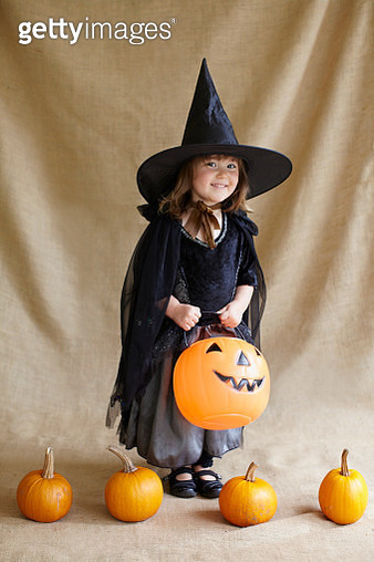 Portrait of girl (2-3) wearing witch costume holding pumpkin - gettyimageskorea