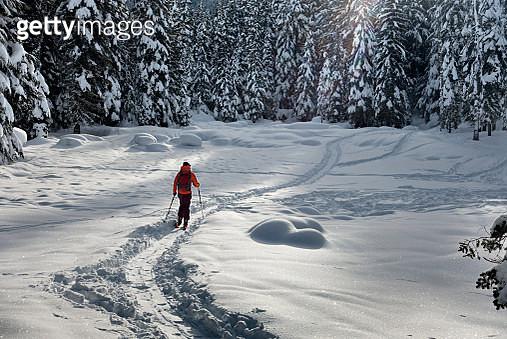Man in red jacket on skis skinning in deep snow - gettyimageskorea